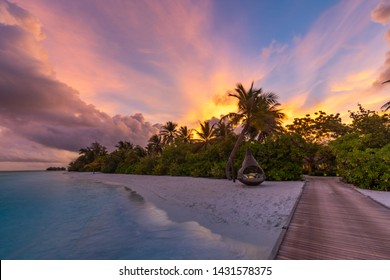 Sunset on Maldives island, luxury water villas resort and wooden pier. Beautiful sky and clouds and beach background for summer vacation holiday and travel concept. Paradise sunset landscape