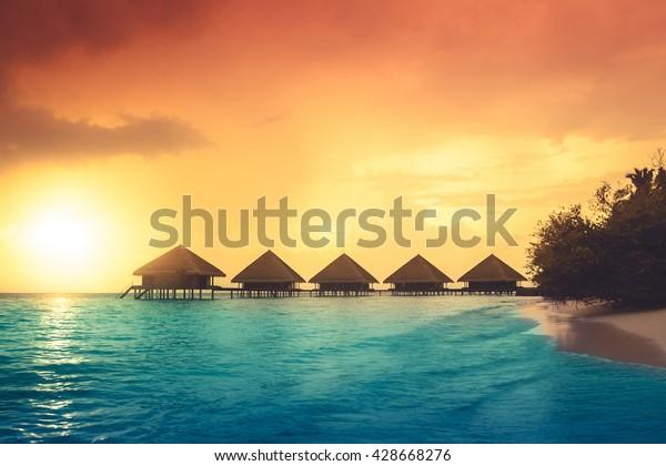 Sunset on Maldives island, water villas resort