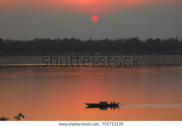 Sunset on the mekong with traditional boat in Kratie, Cambodia