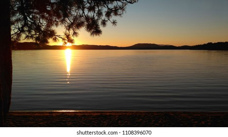Sunset on a mountain lake. View from the pine forest