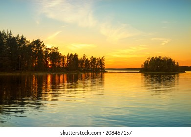 Sunset on the Norwegian lake. Sky reflected on water surface.