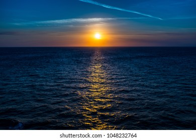 Sunset on the ocean, subdued yellows and blues in the distance