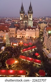Sunset on Old Town Square with St. Teyn gothic cathedral in Prague during Christmas market.