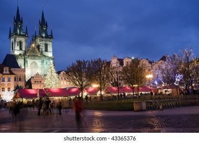 Sunset on Old Town Square with St. Teyn gothic cathedral in Prague during Christmas market with walking people.
