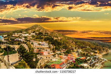 sunset on piled houses on slopes of Ischia island, Naples in Italy