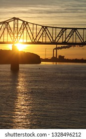 Sunset on the river with bridge and industry in site.