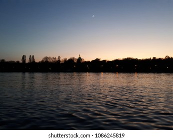 Sunset on a riverbank with gentle waves, night lights and park silhouette.