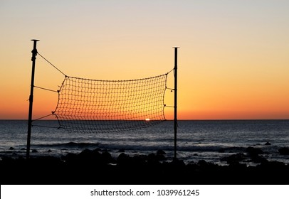 Sunset on the seaside with beach volleyball net.