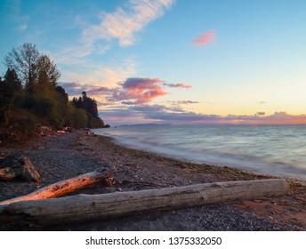 Sunset on Semiahmoo Spit with brilliant orange clouds on a blue sky and a lonley beach strewn with heavy logs, San Juan Islands in the background