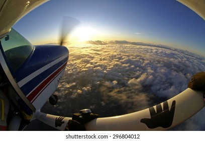 Sunset on a skydive plane above the clouds. Effect made with a fish-eye lens. Photographer hangs on the airplane wing.