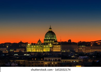 Sunset on the skyline of Rome city, with the dome of St. Peter's Cathedral in the center. Intense yellow-orange color and horizon against the light.