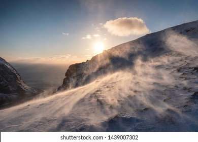 Sunset on snowy hill in blizzard at sunset. Ryten mount, Norway