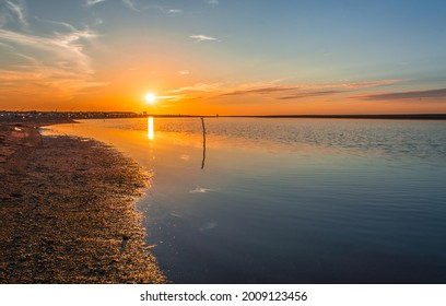 sunset on stagnant river, sunset in calm lake with sandy coast, sun reflection on stagnant lake, stagnant water