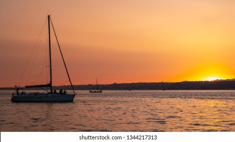 Sunset on the Tagus. A tranquil view of the sun setting over the Tagus River with a foreground yacht taking in the view.