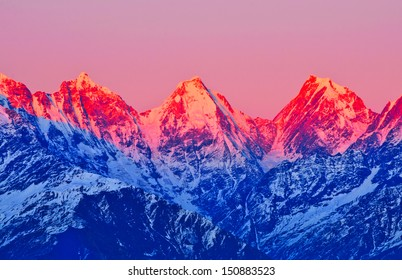 sunset on three mountain peaks in Himalaya