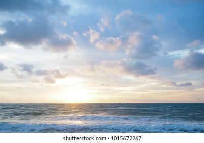 sunset on the tropical beach with beautiful sky, clouds, soft waves