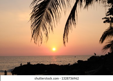 Sunset on tropical sea under palm trees and beach