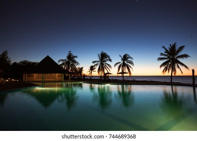 Sunset on a tropical swimming pool overlooking the sea