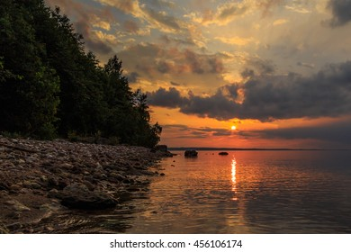 Sunset on the Volga River, the sun sets over the horizon, rocky shore, water light path