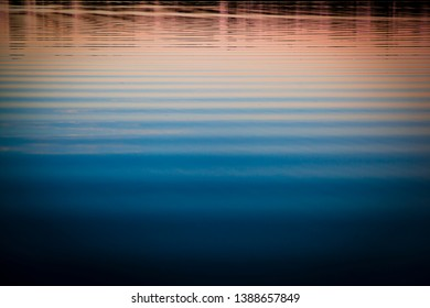 Sunset on water, Colors of setting sun reflected in ripples of water. Bands of blue and warm orange tones.