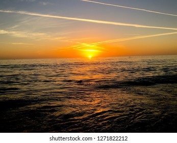 SUNSET ON WATER WITH CONTRAILS