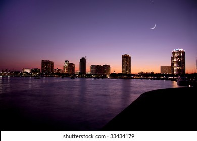 Sunset on the waterfront in St. Petersburg, Florida showing buildings, boats, bay and heron bird in shillouette and cresent moon.  The sky and water shows shades of purple and orange.