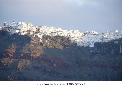 sunset on the white villages on the slopes of the volcano caldera of Thera, Santorini, Greece