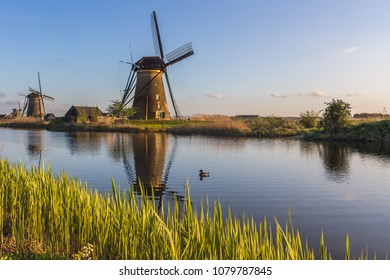 Sunset on windmill reflected in the canal Kinderdijk Molenwaard South Holland The Netherlands Europe