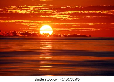 Sunset in the open ocean. Colorful views of the surface of the water and the sky with clouds.Natural Sunset Scene Over ocean.