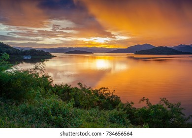 Sunset in orange sky on the river, Keang Krachan Dam, Petchaburee, Thailand