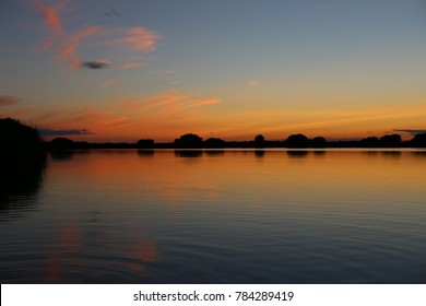 Sunset with an orange sky over the waters of a gravel pit in Greatstone, Romney Marsh, Kent, UK