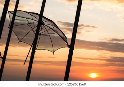 sunset orange sky romantic evening landscape with street outdoor exterior object hanging umbrella on high pillar black silhouette shape, copy space
