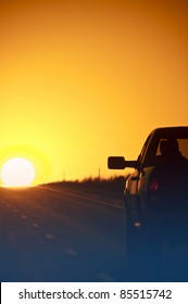 Sunset Outback Highway. Pickup on the Highway - Sunset. Vertical Photo.