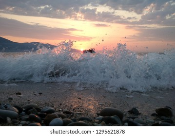 Sunset over the Adriatic sea with waves washing the shore on the foreground and a boat with tourists in the background, Vlora, Albania