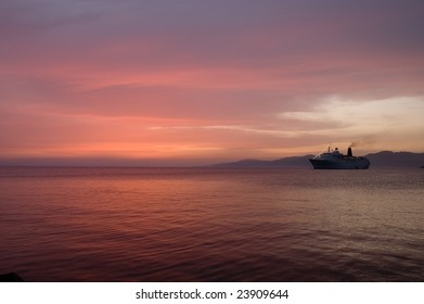 Sunset over Aegean sea with cruise boat in background, Mykonos, Greece