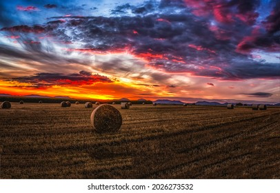 Sunset over an agricultural field with haystacks. Sunset field with haystacks. Haystack field at sunset. Sunset agricultural field landscape