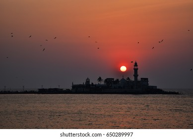 Sunset over the Arabian sea with the silhouette of Haji Ali Dargah mosque located on an islet off the coast of Worli in the southern part of Mumbai with people walking towards it to pray
