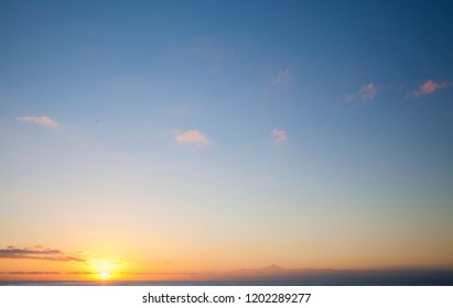 Sunset over Atlantic ocean as seen from Puerto de Las Nieves on Gran Canaria, natural background of predominantly sky, peak of Teide on Tenerife on the lower edge of the picture, light pink clouds