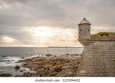 Sunset over the Atlantic ocean. Watchtower of fort of Sao Francisco do Queijo in Porto, Portugal, frequently shortened to Castle of the Cheese, 15th century