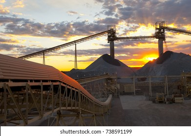 Sunset over Australian mine, late afternoon sunset over mine pile showing a a bright red sun shining on the elevators from the pile the ore gets crushed by a large sagmill.
