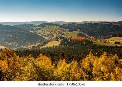 Sunset over autumn forest, fields and meadow in backlight. Evening sunbeams on meadow. Warm sun light in countryside of Bohemian Moravian Highlands, Zdar Hills, Vysocina, Czech Republic.