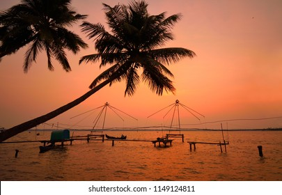 Sunset over backwaters in Kochi with silhouette of coconut trees in the background.