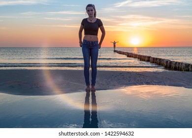sunset over the baltic sea, portrait of a young woman standing on the beach