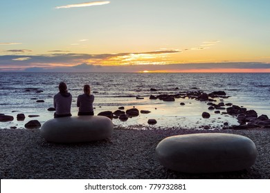 Sunset over Baltic sea in Visby on island of Gotland in Sweden. Beautiful colours, gradients and nature calmness.  Silhouette of man and woman sitting on big stone and looking at the sun, sea. Summer.