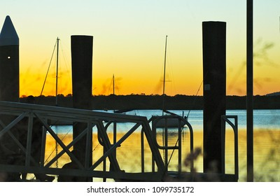 Sunset over a bay, with fishermen sitting on a ferry wharf. The water is blue and gold. Sailing boats are moored in the bay, and hills are in the distance. The sky is golden.