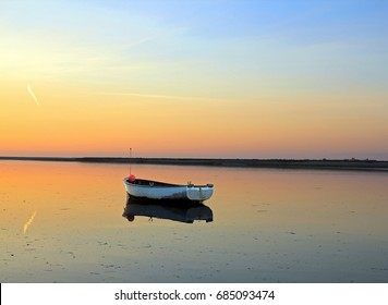 Sunset over the Bay of Somme Hauts-de-France, North, France. Reflections of a boat