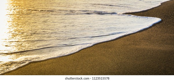 Sunset over the beach with the end of a foamy ocean wave recovering the sand. Wallpaper and backdrop with large copy space.