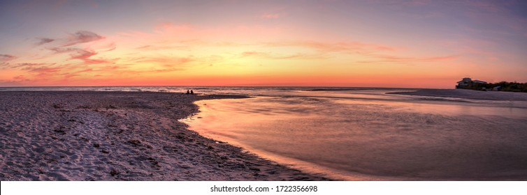 Sunset over the beach as a waterway of Clam Pass leads down to the ocean in Naples, Florida