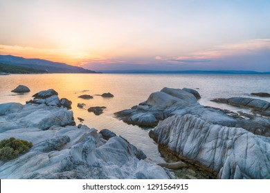 Sunset over the beautiful Coastline Landscape with white stones and clear sea