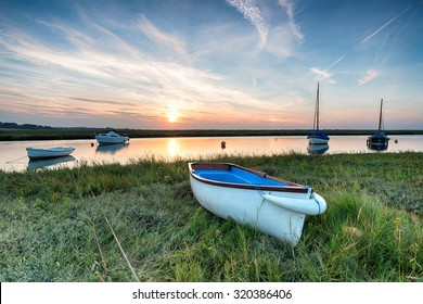 Sunset over boats on the salt marshes at Blakeney on the north coast of Norfolk